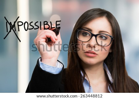 Beautiful woman converting the word impossible to possible - stock photo