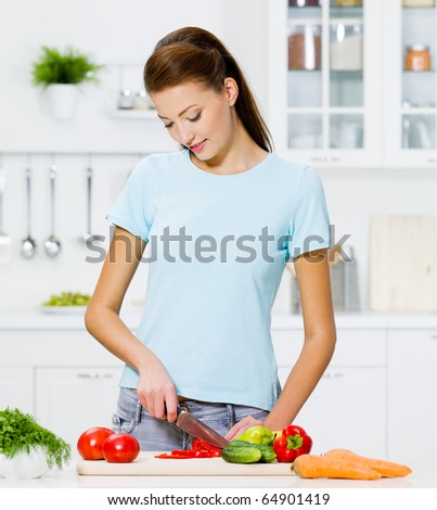 Beautiful woman cooking healthy food in the kitchen - indoors - stock photo