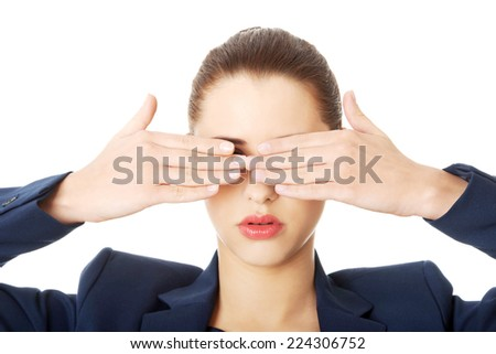 Beautiful woman covering her eyes with her hands - stock photo
