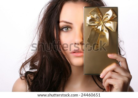 Beautiful woman covers her face with present - stock photo
