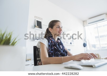 woman office furniture. beautiful woman creative professional is smiling seating on her desk typing a keyboard office furniture n