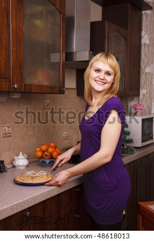 Beautiful woman cutting hot apple pie at kitchen. Portrait of young happy woman with sweets. Young female doling out apple cake indoors. - stock photo