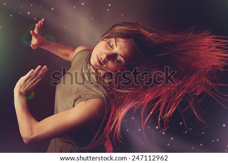 Beautiful woman dancer dancing over dark background with light rays and star swirls and glitters - stock photo