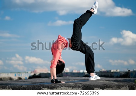Beautiful woman dancing hip-hop modern style over urban city landscape and blue sky
