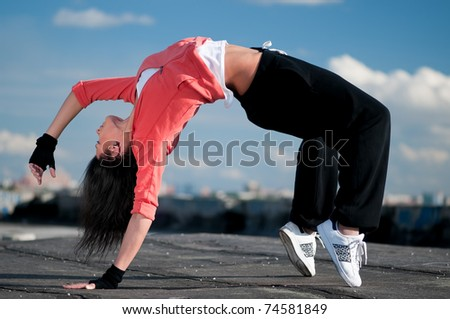 Beautiful woman dancing hip-hop modern style over urban city landscape and blue sky - stock photo