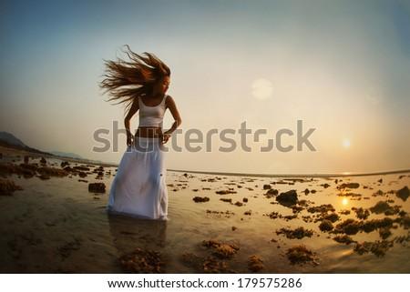 Beautiful woman dancing on the beach at sunset - stock photo