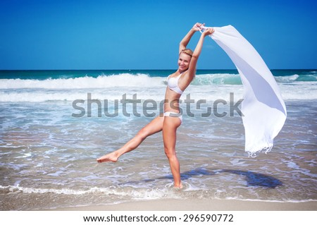 Beautiful woman dancing on the beach wearing stylish swimsuit and holding white scarf, relaxation outdoors on tropical resort, enjoying freedom and summer vacation - stock photo