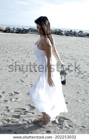 Beautiful woman dancing on the beach with white dress and shoes in hand