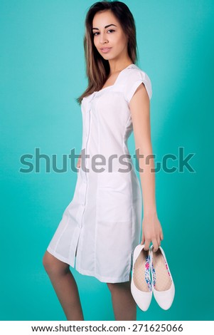 Beautiful woman doctor holding a hand shoes on turquoise background - stock photo