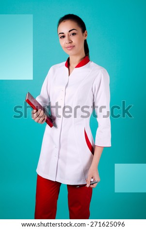 Beautiful woman doctor holding red trousers on turquoise background - stock photo