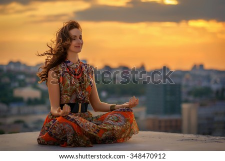 Beautiful woman doing a yoga exercise on he rooftop of a skyscraper at sunset - stock photo