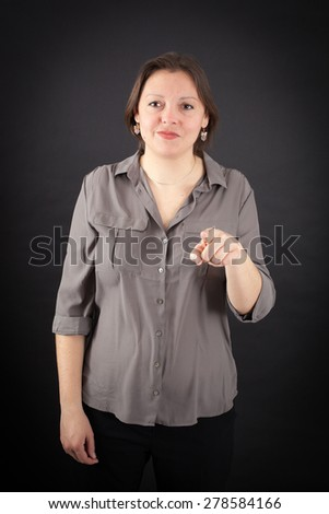 Beautiful woman doing different expressions in different sets of clothes: pointing - stock photo