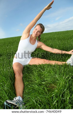 Beautiful woman doing fitness exercises in nature - stock photo
