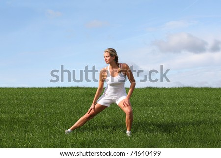 Beautiful woman doing fitness exercises in nature