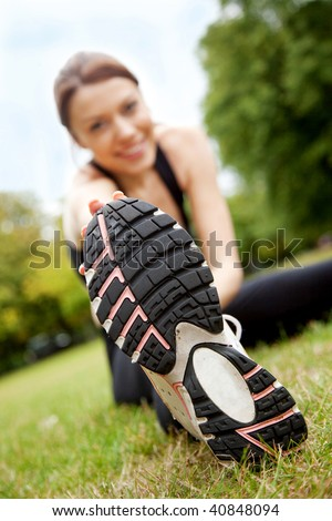 Beautiful woman doing gym stretches on the grass outdoors - stock photo