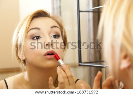 Beautiful woman doing makeup on her face in mirror - stock photo