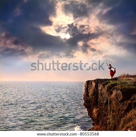 Beautiful woman doing natarajasana dancer yoga pose on the cliff near the ocean with dramatic sky at background in India - stock photo