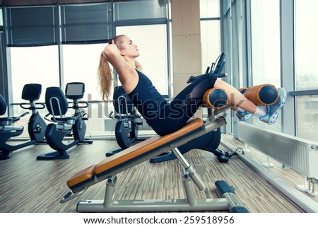 Beautiful woman doing press fitness exercise at sport gym. - stock photo
