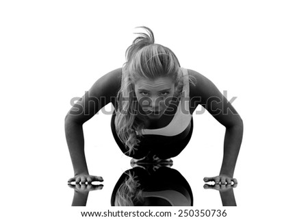 Beautiful woman doing push ups on beach against mirror - stock photo