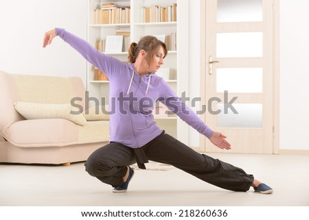 Beautiful woman doing qi gong tai chi exercise at home - stock photo