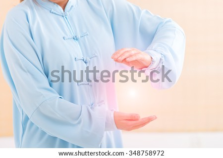 Beautiful woman doing qi gong tai chi exercise or reiki wearing professional, original Chinese clothes at gym - stock photo