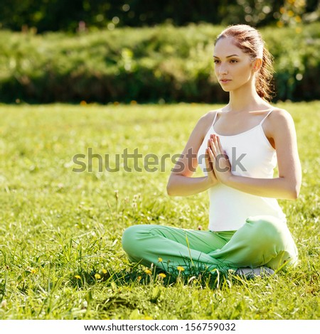 Beautiful Woman doing Yoga Exercises in the Park. - stock photo