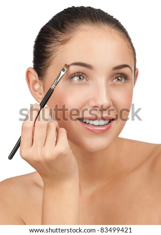 Beautiful woman drawing a shape of her eyebrows using cosmetic brush