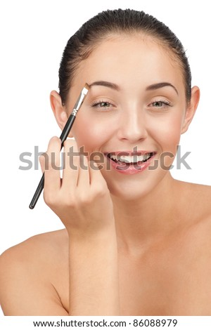 Beautiful woman drawing a shape of her eyebrows using cosmetic brush - stock photo