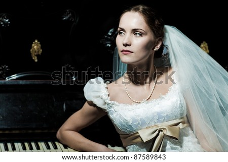 beautiful woman dressed as a bride standing next to piano - stock photo