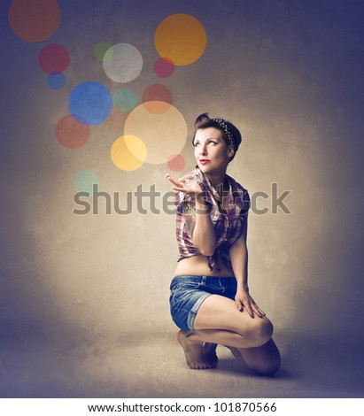 Beautiful woman dressed as a pinup with colored circles in the background - stock photo