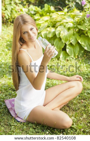 Beautiful Woman Drink Water In Nature, Green Environment - stock photo
