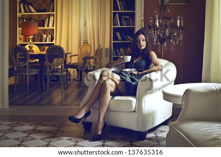 beautiful woman drinking a cup of tea in an ancient living room - stock photo