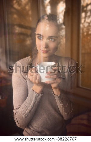 beautiful woman drinking coffee in the morning sitting by the window. view from outside. - stock photo