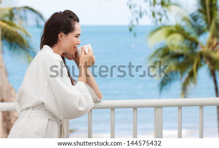 Beautiful woman drinking her morning coffee or tea on a tropical balcony. - stock photo
