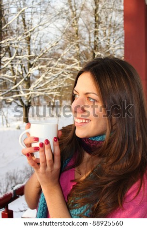Beautiful woman drinking hot tea/coffee on winter background