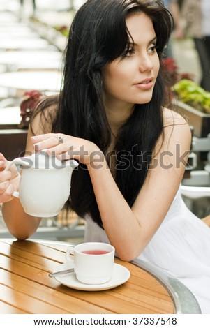 Beautiful woman drinking tea in a cafe - stock photo