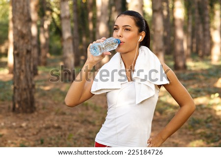Beautiful woman drinking water from plastic bottles after running - stock photo