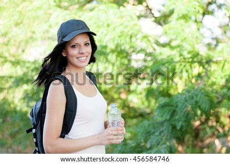 Beautiful woman drinking water while hiking through the countryside