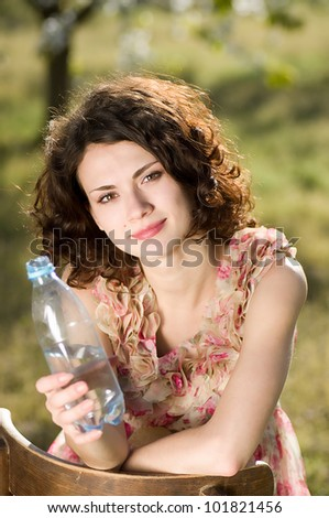 Beautiful woman drinks cold water in spring garden