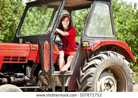 Beautiful woman driving tractor