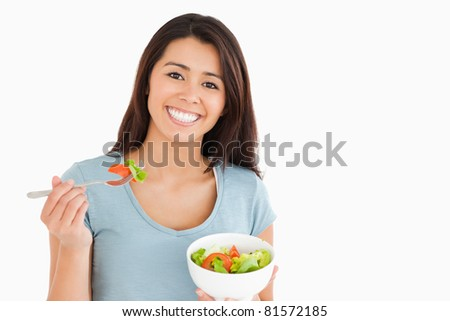 Beautiful woman eating a bowl of salad while standing against a white background - stock photo