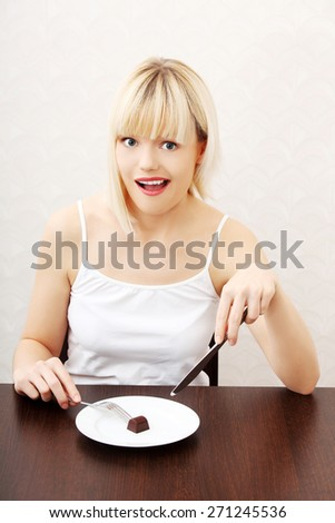 Beautiful woman eating a piece of chocolate. - stock photo