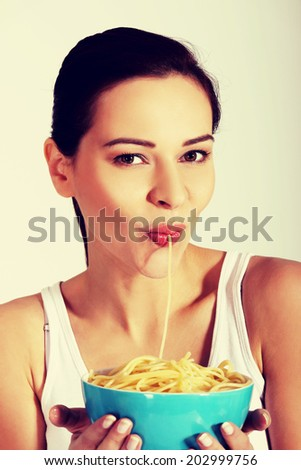 Beautiful woman eating pasta from a bowl. - stock photo