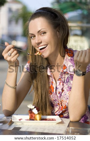 beautiful woman eating pie in cafe - stock photo