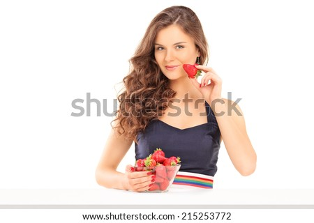 Beautiful woman eating strawberries seated at a table isolated on white background - stock photo