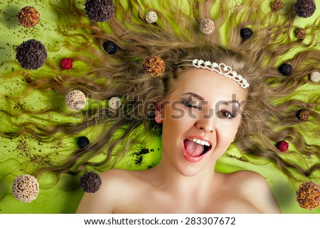 Beautiful woman eating tasty candies - stock photo