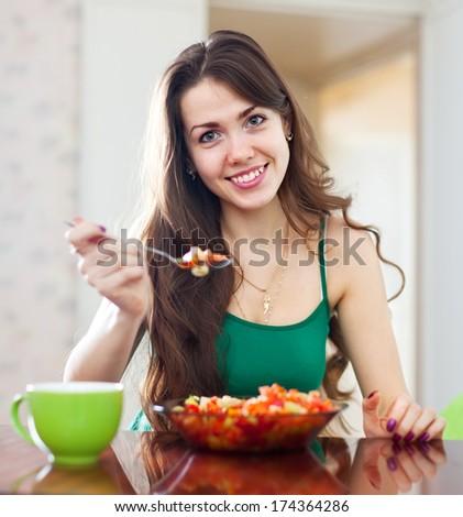 beautiful woman eating veggie salad at home - stock photo