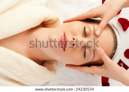 Beautiful woman enjoying a face massage competently carried out in a spa
