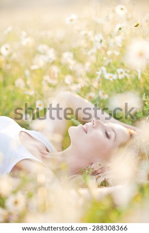 Beautiful woman enjoying daisy field, nice female lying down in meadow of flowers, pretty girl relaxing outdoor, having fun, holding plant, happy young lady dansing in spring green nature - stock photo