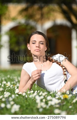 Beautiful woman enjoying daisy field, nice female lying down in the meadow of flowers, girl relaxing outdoor, having fun, holding plant, Relaxing young lady and spring green nature, harmony concept - stock photo